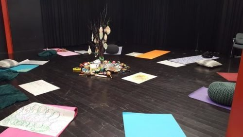 drawing in a circle on yoga mats, with a collection of colourful materials in the middle of the circle